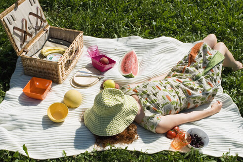Young woman lying on picnic blanket, elevated view - LDF00205