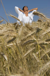 Young man standing in cornfield, hand on hand - LDF00193