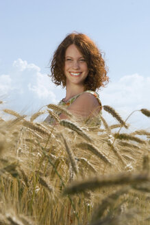 Young woman standing in cornfield, smiling - LDF00187