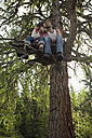 Young couple sitting on tree house, kissing - BABF00224