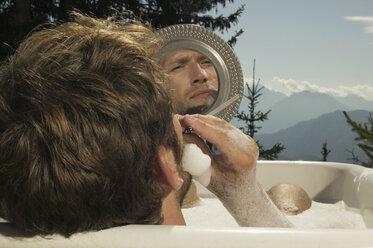 Young man lying in bathtub, shaving - BABF00164