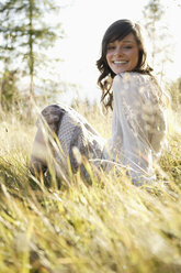Young woman sitting in meadow - BABF00125