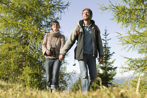 Young couple walking in meadow holding hands - BABF00107