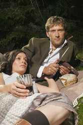 Young couple lying in meadow, having picnic - BABF00074