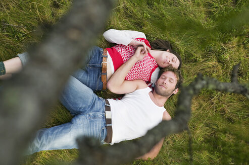 Young couple lying in meadow, eyes closed, elevated view - BABF00032