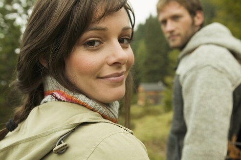 Germany, Bavaria, young woman smiling, man in background, close-up, portrait - BABF00017