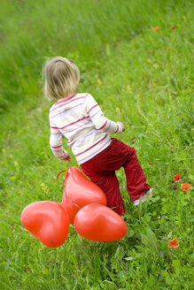 Girl ( 3-4 ) holding bunch of balloons, walking in meadow, rear view - SMOF00083