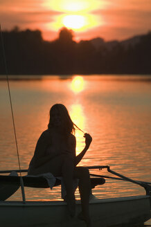 Woman sitting on sailing boat at sunset - ABF00113