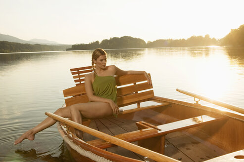 Young woman sitting on rowing boat in lake - ABF00110