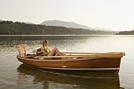 Young woman sitting on rowing boat in lake - ABF00107