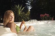 Woman in bathtub holding drink, smiling, portrait - ABF00101