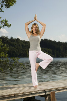 Woman exercising yoga on jetty - ABF00080