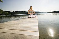 Woman exercising yoga on jetty - ABF00077