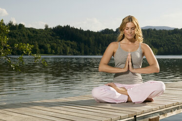 Woman exercising yoga on jetty - ABF00074