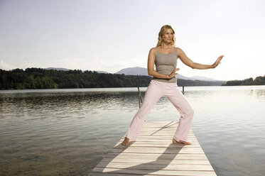 Woman exercising yoga on jetty - ABF00071