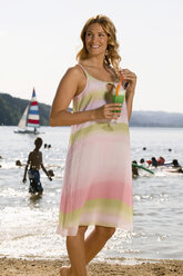 Woman holding cocktail at lake, smiling - ABF00065
