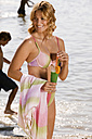 Woman holding cocktail at lake, smiling - ABF00062