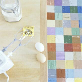 Electric mixer, eggs, flour and baking powder on kitchen table - COF00073