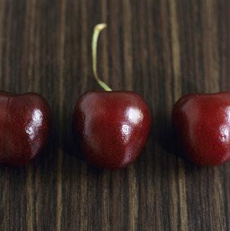 Three cherries in row, close-up - COF00049