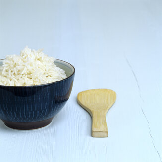 Cooked rice in a dish, wooden spoon aside - COF00043