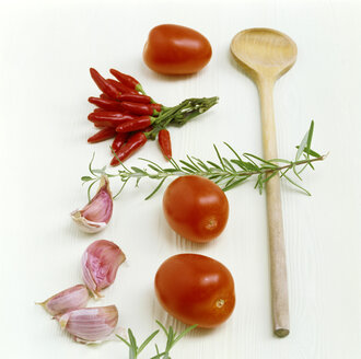 Tomatoes, chillies, garlic, rosemary and wooden spoon on kitchen table - COF00040