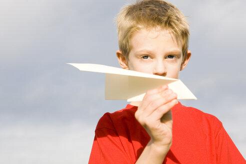 Boy (10-12) holding paper plane - RDF00210