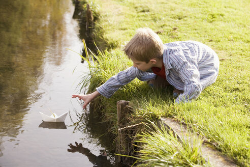 Boy (10-12) putting paper boat in river - RDF00174