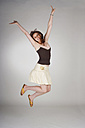 Young woman jumping arms up - MFF00298