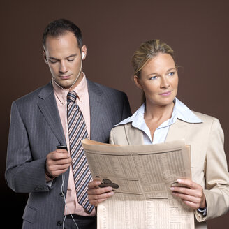 Businessman and businesswoman, man listening to mp3 player, woman holding newspaper - JLF00249