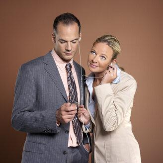 Businessman and businesswoman listening to mp3 player - JLF00246