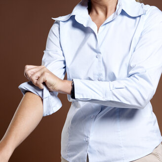 Businesswoman rolling up shirt sleeves, close-up - JLF00225