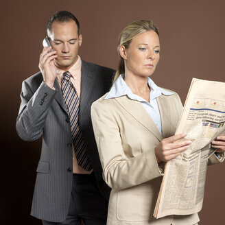Businessman and businesswoman man using mobile phone, woman holding newspaper - JLF00219