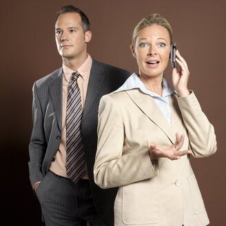 Businessman and businesswoman, woman holding mobile phone - JLF00213