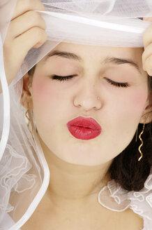 Young bride giving kiss, eyes closed - 00181LR-U
