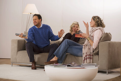 Parents with daughter sitting on sofa in living room - WESTF03326