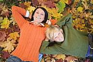 Mother and son (8-11) lying on autumn leaves, elevated view, portrait - WESTF03110