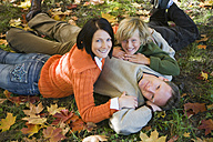 Parents with son (10-12) lying in meadow, portrait, elevated view - WESTF03103