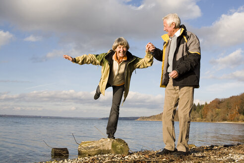 Senior couple hand in hand, woman standing on tree trunk - WESTF03507