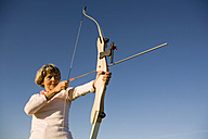 Senior adult woman using bow and arrow - WESTF03468