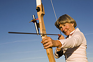 Senior adult woman using bow and arrow - WESTF03465