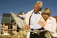 Senior couple holding plan in front of partially built house - WESTF03456