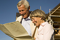 Senior couple holding plan in front of partially built house - WESTF03453
