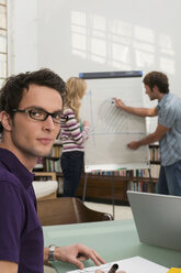 Young man explaining woman chart in background, focus on man smiling - WESTF03625