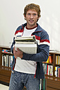 Young man standing with holding books, portrait - WESTF03613