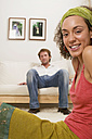 Young woman sitting on floor, young man in background - WESTF03610