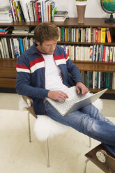 Young man sitting on chair, using laptop - WESTF03607