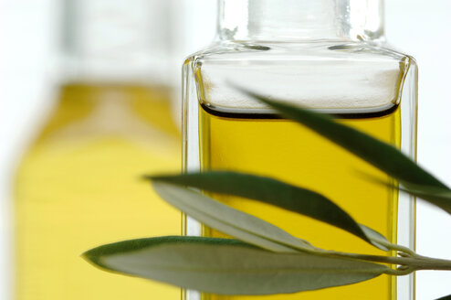 Bottle of olive oil with twig, close-up - ASF02891