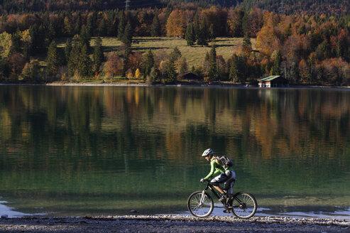 Woman mountain biking at lake - MRF00794