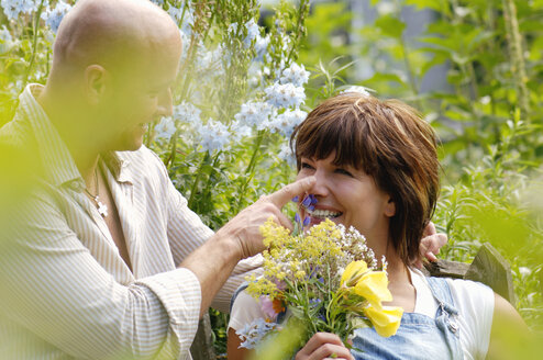 Couple in garden with woman holding bunch of flowers - HHF00892