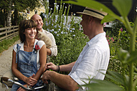 Couple sitting on bicycle, talking to neighbor - HHF00889